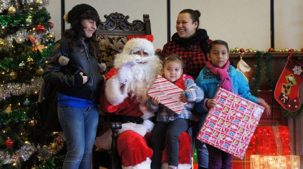 A local family poses with Santa Claus for a free holiday photo provided by the BYNC.  (The Gate/Adriana Cardona-Maguigad)